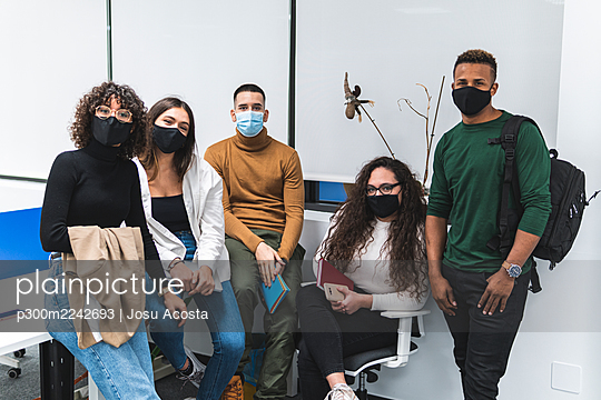 Male and female colleagues wearing protective face mask against white wall in office - p300m2242693 by Josu Acosta