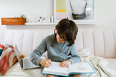 Boy drawing on notebook on sofa at home by laptop with instructions - p1166m2224155 by Cavan Images
