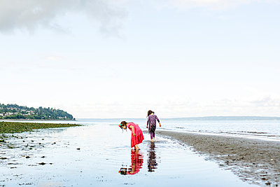 Wide angle view of two girls exploring the beach at Carkeek Park - p1166m2289952 by Cavan Images