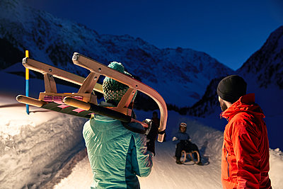 Couple with sledge in sw-covered landscape at night - p300m1587644 by Christian Vorhofer