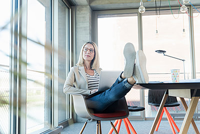 Relaxed businesswoman using laptop in office with feet up - p300m2103912 by Uwe Umstätter
