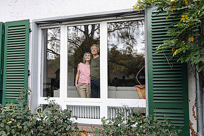 Senior couple behind windowpane of their home looking out - p300m2155044 by Gustafsson