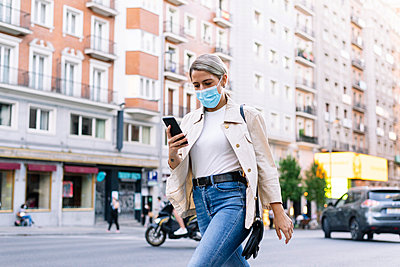 Young woman wearing mask using mobile phone while walking on street in city - p300m2221180 by Jose Luis CARRASCOSA
