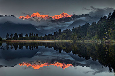 Sunset reflection of Lake Matheson with Mount Tasman and Mount Cook - p884m863964 by Colin Monteath/ Hedgehog House