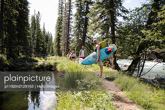 Surfer friends carrying surfboards in sunny woods - p1192m2129163 by Hero Images