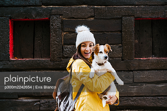 Portrait of smiling woman in yellow raincoat holding dog in front of log cabin - p300m2242654 by Eva Blanco