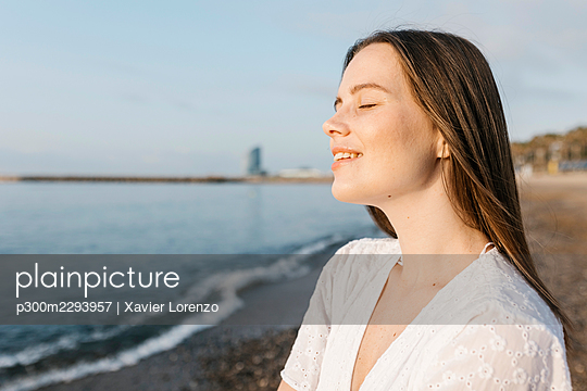 Smiling young woman with eyes closed at beach - p300m2293957 by Xavier Lorenzo