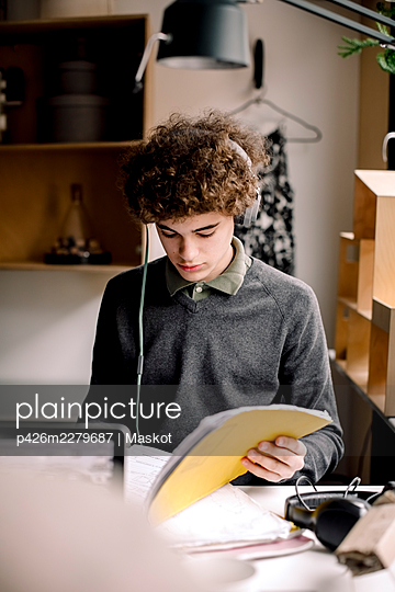 Boy wearing headphones while studying at home - p426m2279687 by Maskot