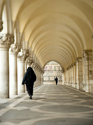 Piazza San Marco is a large square surrounded by arcades and a series of columns. Two people walking.  - p1100m991384f by Mint Images