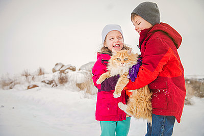 Happy siblings carrying cat while standing on snow during winter - p1166m2024817 by Cavan Images