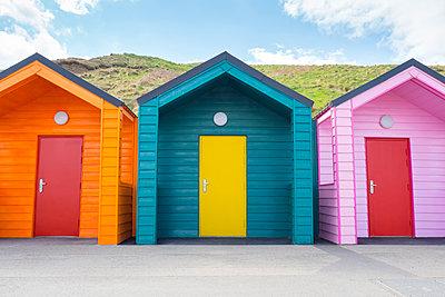 Three brightly coloured beach huts - p1302m1573489 by Richard Nixon