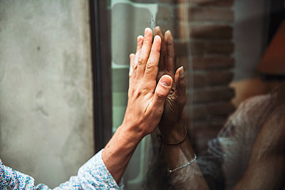 Close-up of couple hands touching each other through cafe's window - p300m2214002 by klublu
