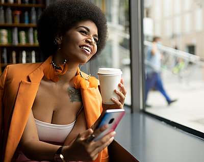 Happy woman with smart phone and coffee cup looking through window in cafe - p300m2252062 by Jose Carlos Ichiro