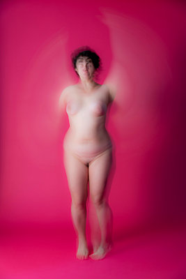 Naked woman in studio, blurred on pink background - p590m2054311 by Philippe Dureuil