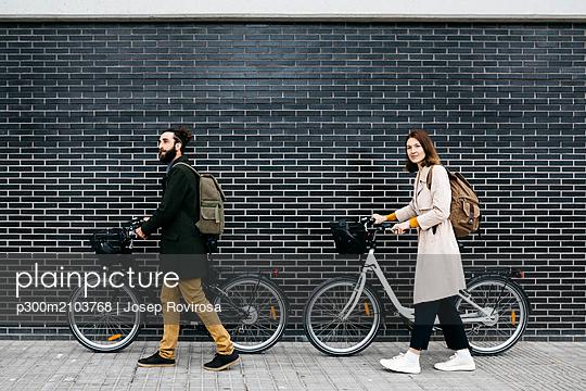 Couple pushing e-bikes along a brick wall - p300m2103768 by Josep Rovirosa