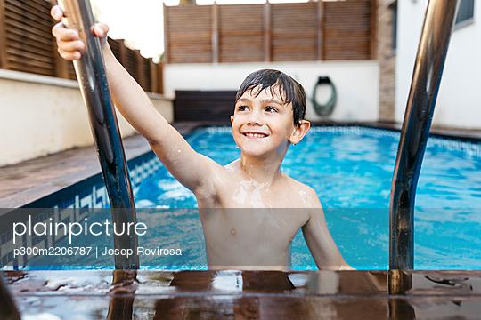Smiling boy holding ladder in swimming pool - p300m2206787 by Josep Rovirosa