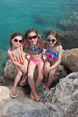 Drei supercoole Mädchen sitzen am Wasser - p045m1591425 von Jasmin Sander