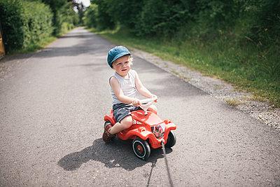 Kleiner Junge auf einem Bobbycar - p1046m1220965 von Moritz Küstner