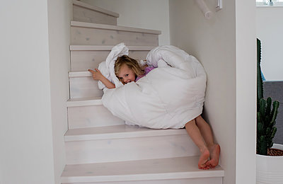 young blonde girl playing wrapped up in a duvet cover on the stairs - p1166m2129933 by Cavan Images