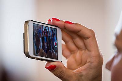 Woman shooting video with smart phone - p1418m1474957 by Jan Håkan Dahlström