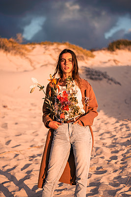 Young woman on the beach with flowers in waistband - p1640m2246084 by Holly & John