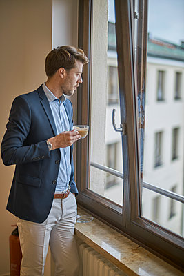Businessman with cup of coffee looking out of window - p300m1587942 by Benjamin Egerland