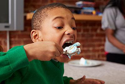 Black boy eating cake at table - p555m1413151 by Granger Wootz