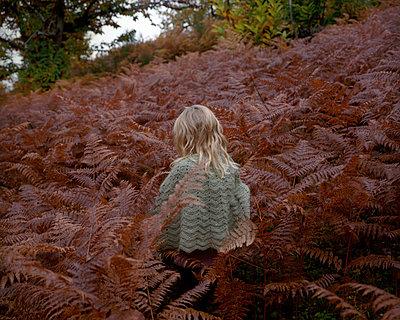 Girl walking through fern field - p945m1196294 by aurelia frey