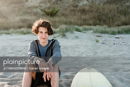 long haired teenager sitting next to surfboard on a beach in New Zealand - p1166m2208044 by Cavan Images