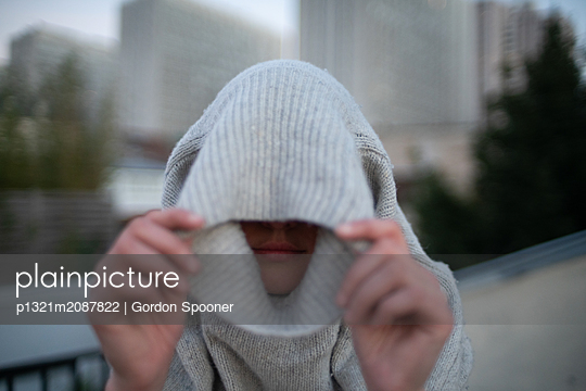 Woman pulls wool sweater over her head - p1321m2087822 by Gordon Spooner