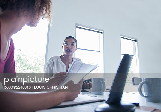 Female entrepreneur with paper standing by colleague at office - p300m2240018 by LOUIS CHRISTIAN