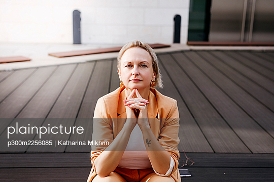 Mature female entrepreneur with hands clasped sitting on floorboard - p300m2256085 by Katharina Mikhrin