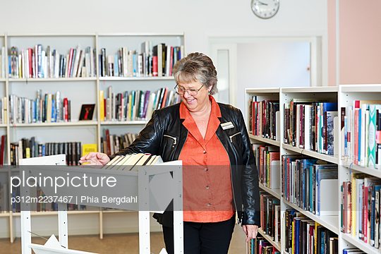 Smiling woman in library - p312m2237467 by Phia Bergdahl