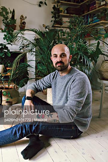Portrait of man sitting on hardwood floor against plants at home - p426m2101770 by Maskot