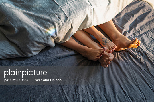 Couple's feet sticking out from under duvet in bed - p429m2091228 by Frank and Helena