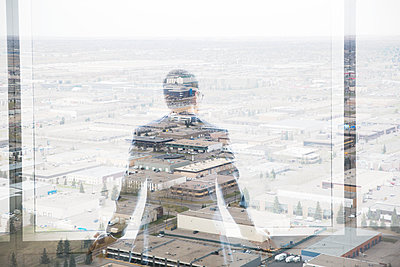 Digital composite businessman looking over industrial buildings - p1192m1116645f by Hero Images