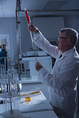 Male scientist experimenting in laboratory - p1315m2041226 by Wavebreak