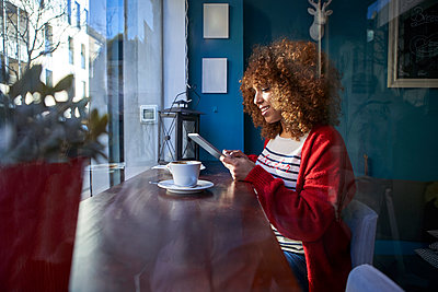 Woman smiling while using digital tablet sitting at cafe - p300m2257336 by Veam