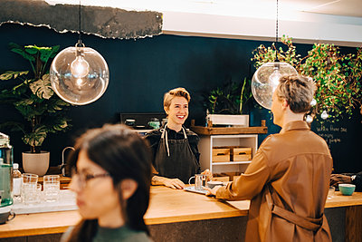 Smiling businesswoman talking with female customer at table in coffee shop - p426m2259498 by Maskot