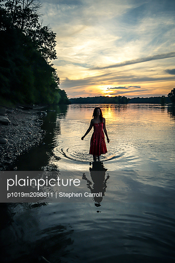Sunset, Woman in river - p1019m2098811 by Stephen Carroll