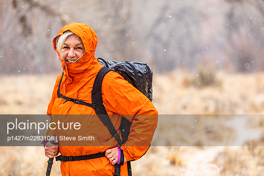 USA, Utah, Escalante, Woman hiking during snow flurry in Grand Staircase-Escalante National Monument - p1427m2283106 by Steve Smith