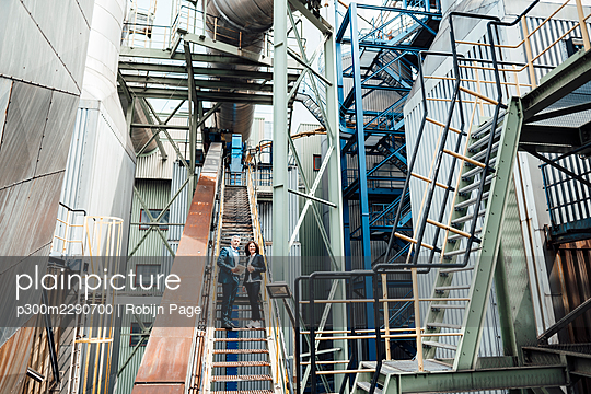 Male and female professionals standing on staircase at workshop - p300m2290700 by Robijn Page