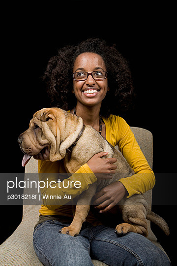 A young woman with her Shar-Pei, studio shot - p3018218f by Winnie Au