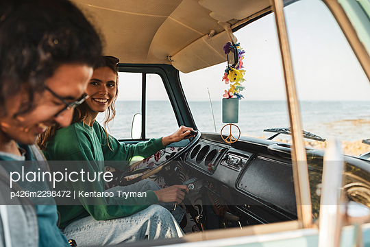 Smiling woman talking with male friend while sitting in camping van during road trip - p426m2298472 by Kentaroo Tryman