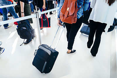 Rear view of businesswomen with luggage walking at airport - p1264m1122096f by Astrakan