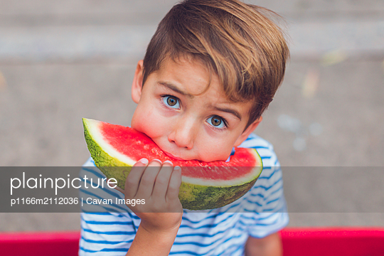 Close-up portrait of boy eating watermelon while sitting outdoors - p1166m2112036 by Cavan Images