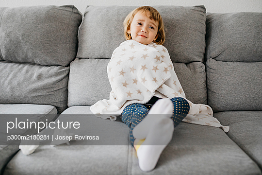 Portrait of sick little girl sitting on the couch at home wrapped in blanket - p300m2180281 by Josep Rovirosa