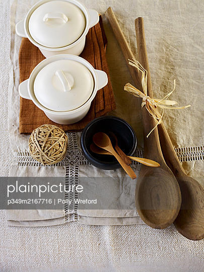 Wooden spoons and ceramic pots with elastic ball band on linen placemats. - p349m2167716 by Polly Wreford