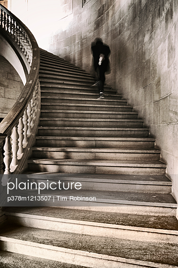 Man walking up staircase - p378m1213507 by Tim Robinson