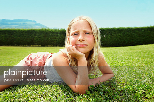 Curious girl laying in grass - p42917303f by Massimo Zen